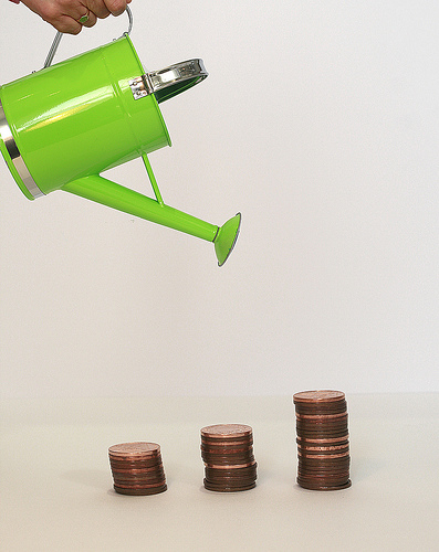 Green watering can that waters money coins