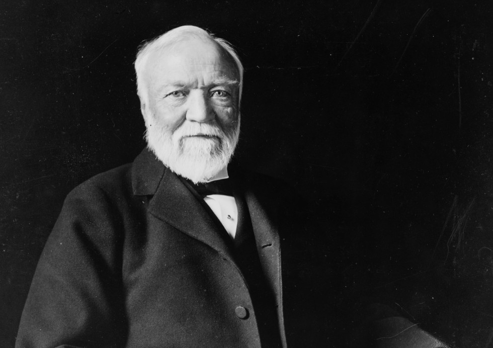 Photo of Andrew Carnegie sitting in chair in front of a black background