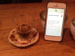 The Cross-Cultural Compass e-book shown on an iPhone on a wooden table with a coffee