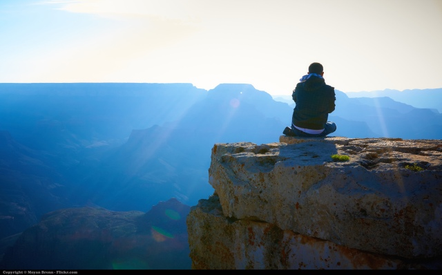 Leader meditating on a mountain top in the sun